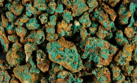Accumuli di malachite aderenti alla superficie di piccole pietre e grumi di idrossido ferroso.